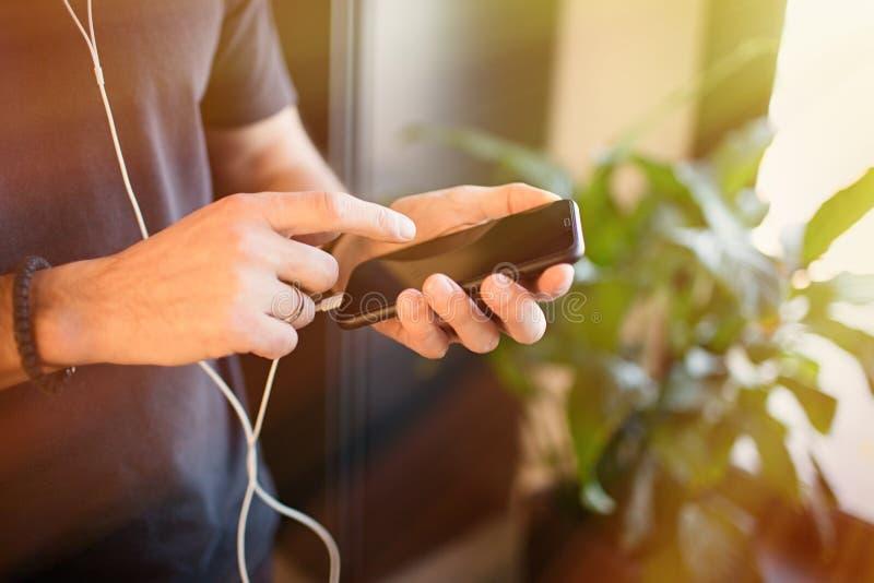 Manlig handinnehavmobiltelefon som hemma kontrollerar sociala n?tverk p? smartphonen signalljus royaltyfria foton