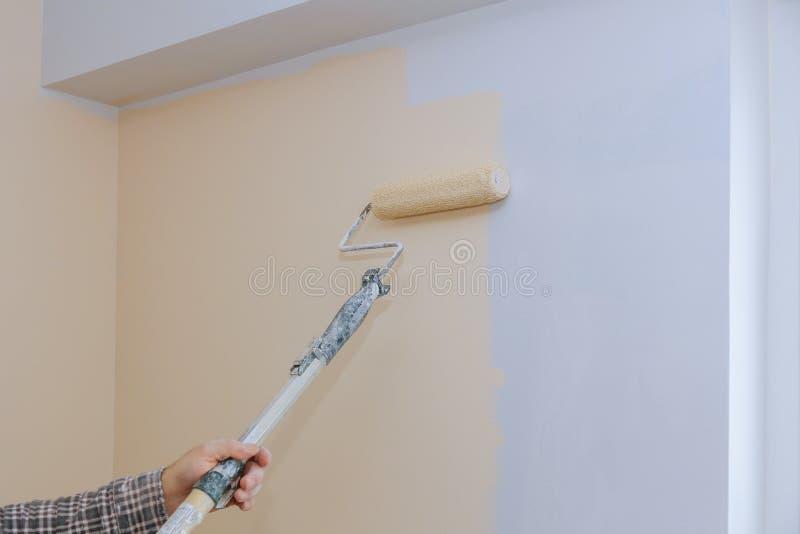 Manlig handmålningvägg med målarfärgrullen Måla lägenheten som renoverar med färgmålarfärg arkivfoton
