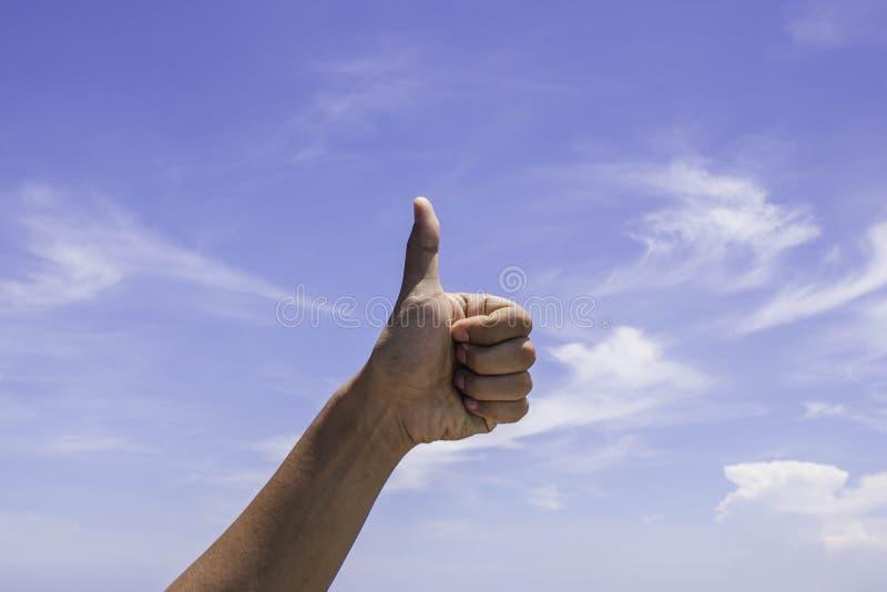 Manlig handvisningtumme upp tecken på blå himmel arkivfoton