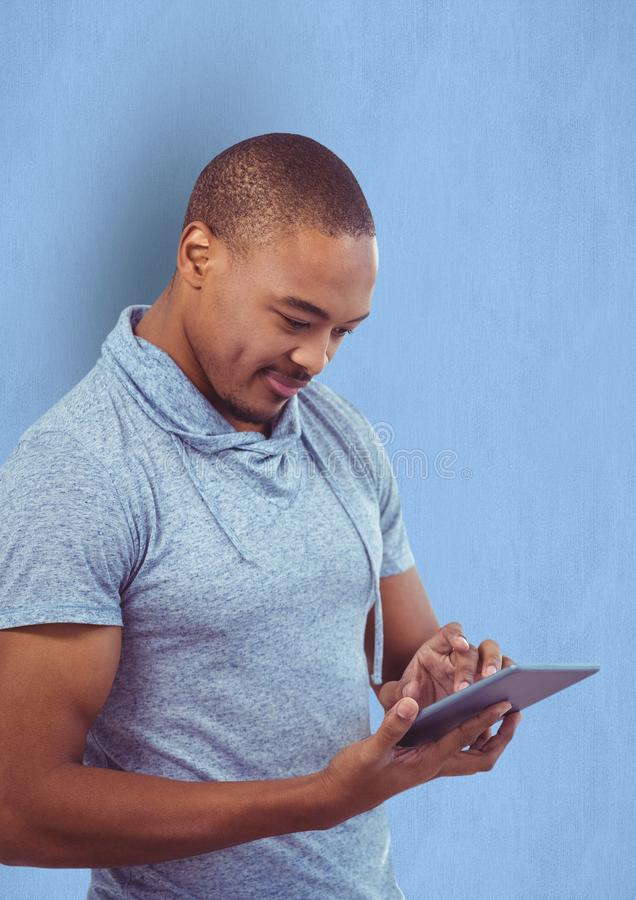 Manlig hipster som använder den digitala minnestavlan mot blå bakgrund arkivfoto
