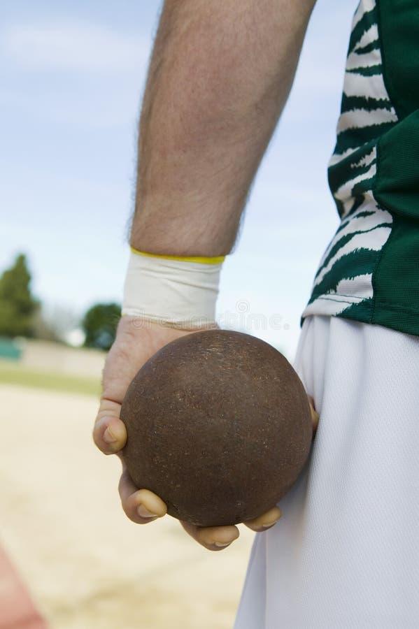 Manlig idrottsman nen Holding Shot Put arkivfoto