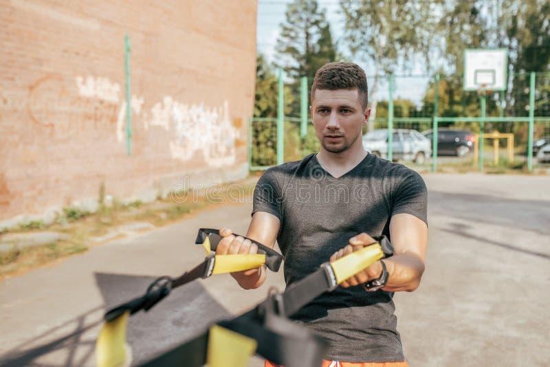 Manlig idrottsman nen, i sommaren i staden på sportjordning Kopplat in i kondition med gummiöglor, remmar för muskler royaltyfri fotografi