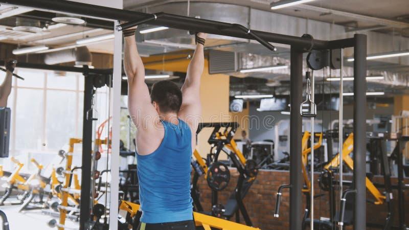 Manlig idrottsman nen - kroppsbyggare som gör buk- övning för handtag-uppstång i idrottshall royaltyfria foton