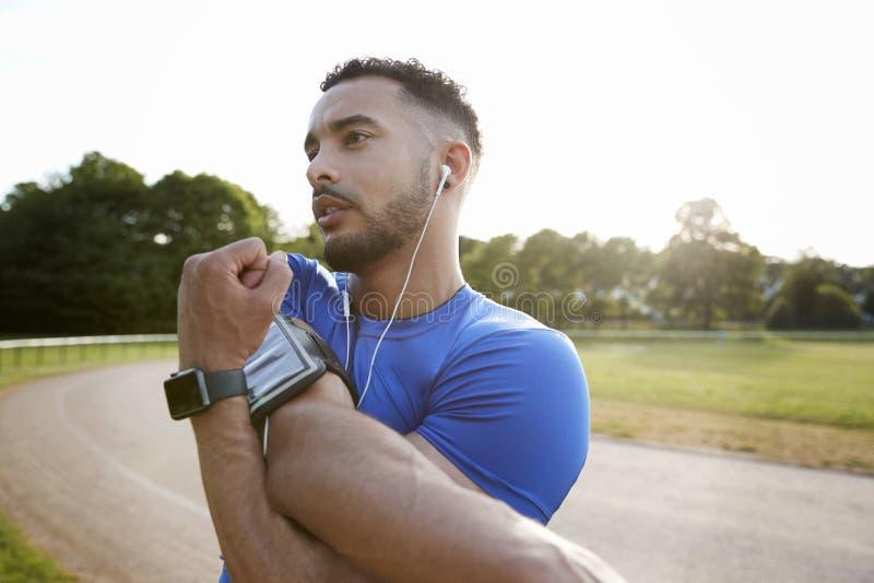 Manlig idrottsman nen på spåret som sträcker upp skuldror, slut royaltyfri fotografi