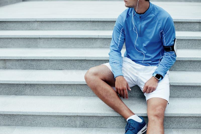 Manlig idrottsman nen som sitter på trappan, armbindel med mobiltelefonen och hörlurar med musik för utbildning royaltyfria foton