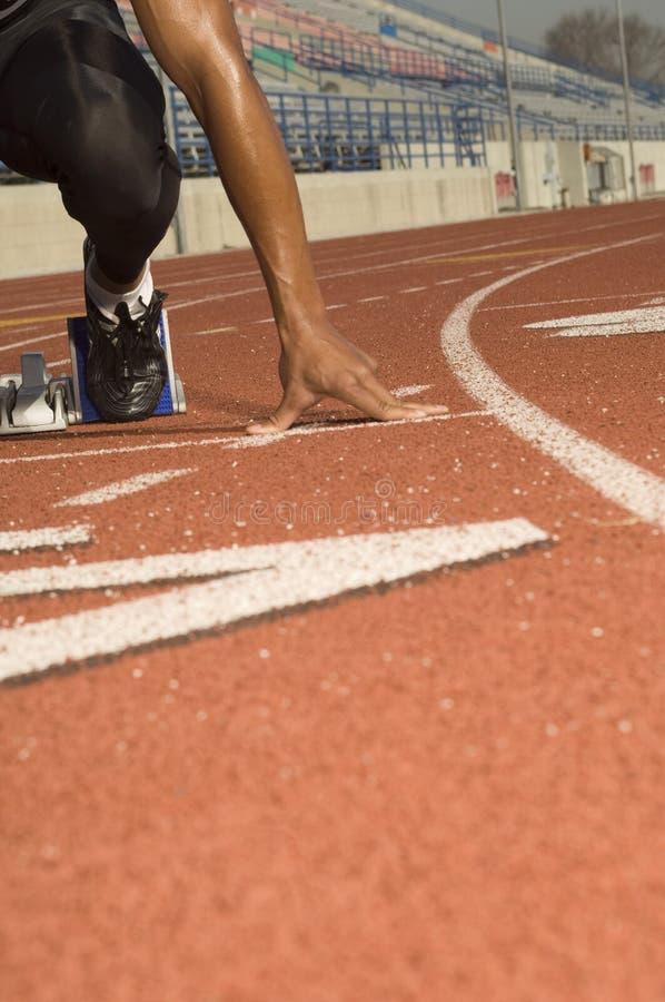 Manlig idrottsman nen At Starting Line som är klar att springa royaltyfria foton
