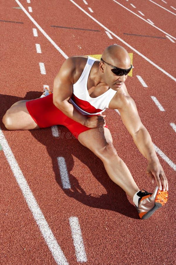 Manlig idrottsman nen Stretching On Racetrack royaltyfri fotografi
