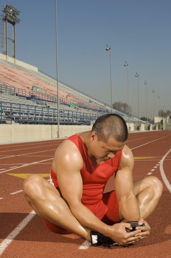 Manlig idrottsman nen Stretching On Racetrack royaltyfria bilder