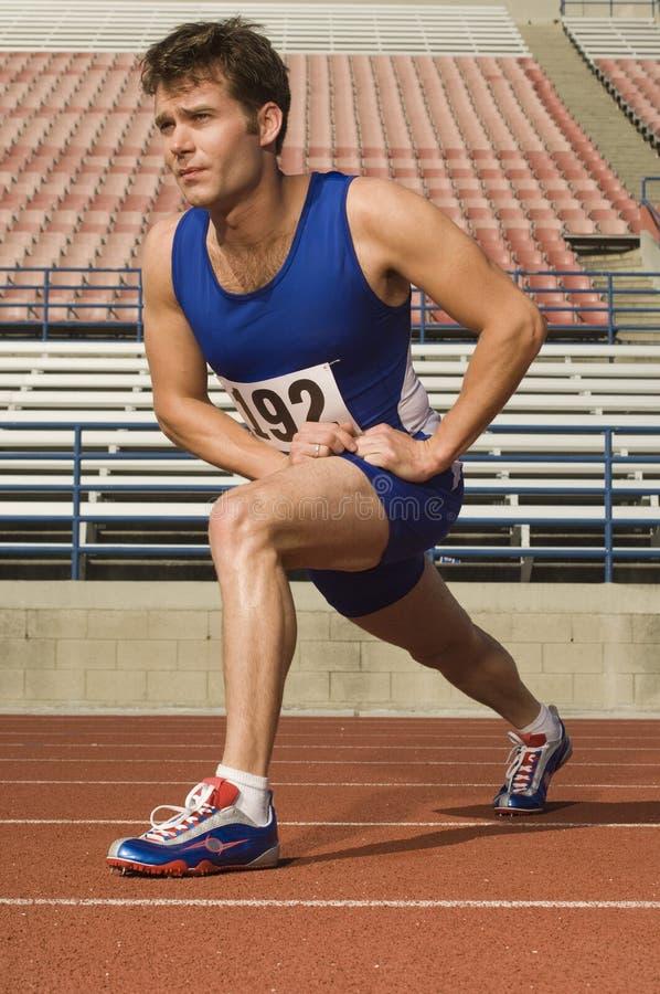 Manlig idrottsman nen Stretching In Stadium arkivfoton