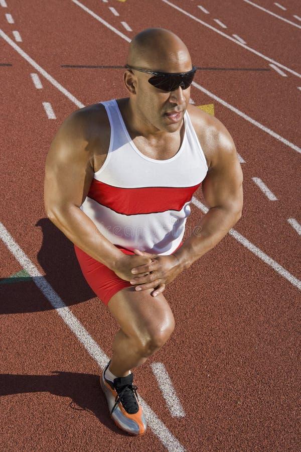 Manlig idrottsman nenStretching On Race kurs arkivbilder