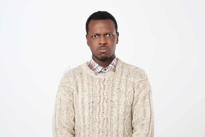 Manlig iklädd varm tröja för afrikansk amerikan som ser kameran med allvarligt och ledset uttryck royaltyfri bild