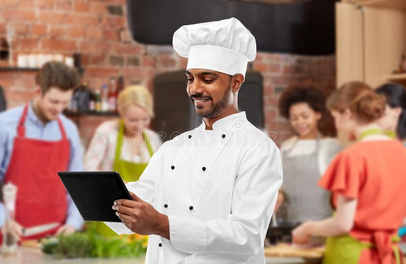 Manlig indisk kock med minnestavlaPC p? matlagninggrupp royaltyfri bild