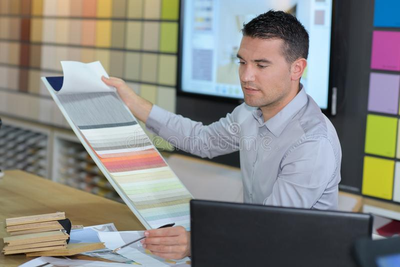 Manlig inreformgivare på skrivbordet arkivbild