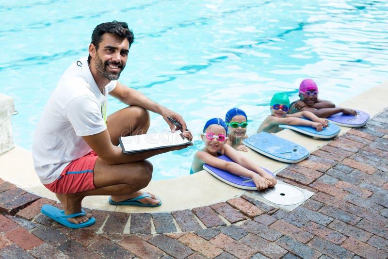 Manlig instruktör med små simmare på poolsiden arkivfoto