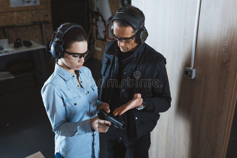 manlig instruktör som beskriver vapnet till den kvinnliga kunden fotografering för bildbyråer