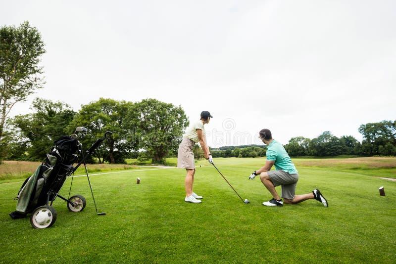 Manlig instruktör som hjälper kvinnan, i att lära golf arkivbild