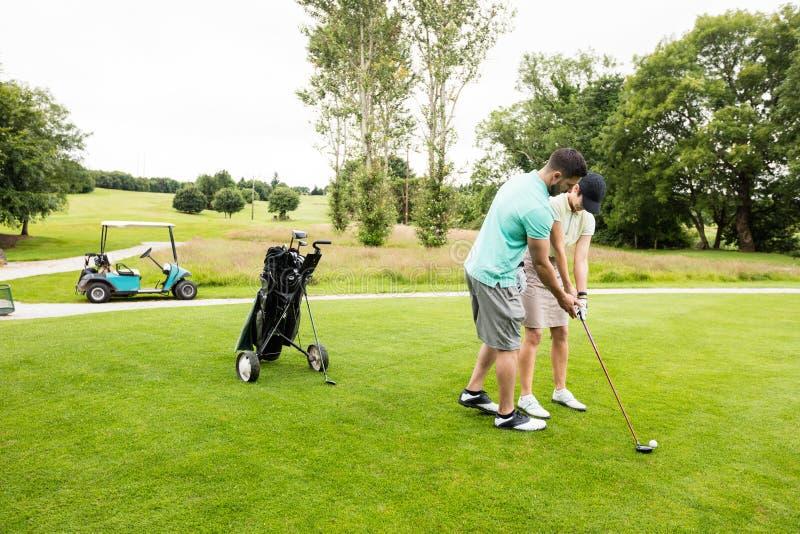 Manlig instruktör som hjälper kvinnan, i att lära golf royaltyfria bilder