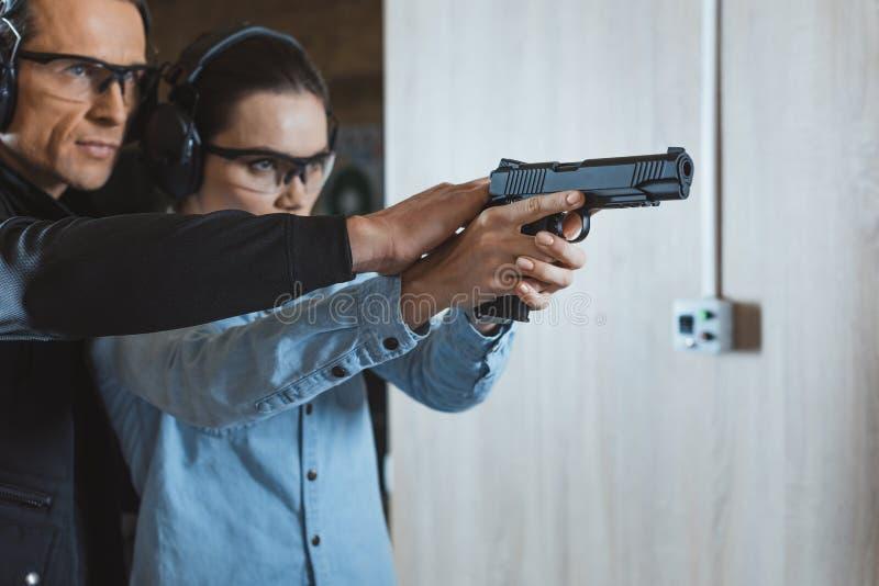 manlig instruktörportionkund som ska skjutas med vapnet arkivfoton