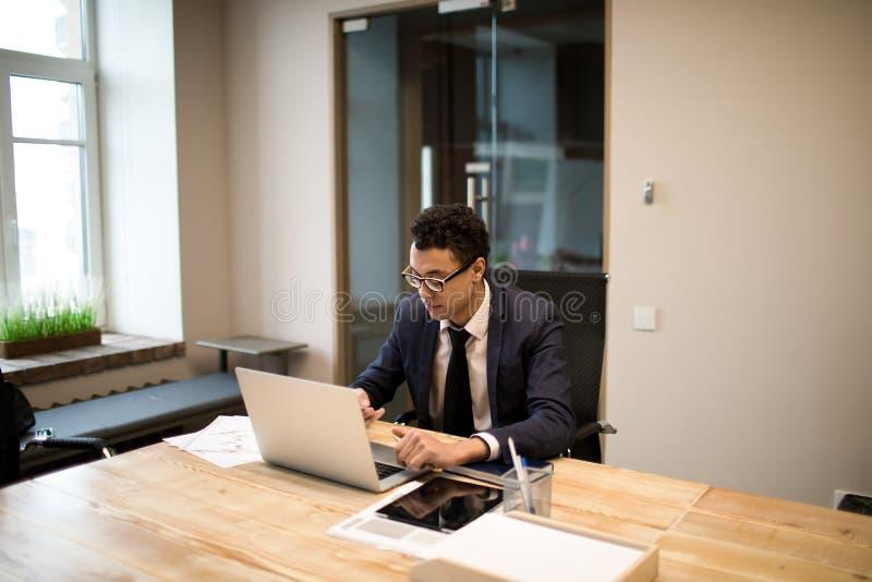 Manlig intelligent anställd som använder applikationer på anteckningsboken under arbetsdag i företag royaltyfri bild