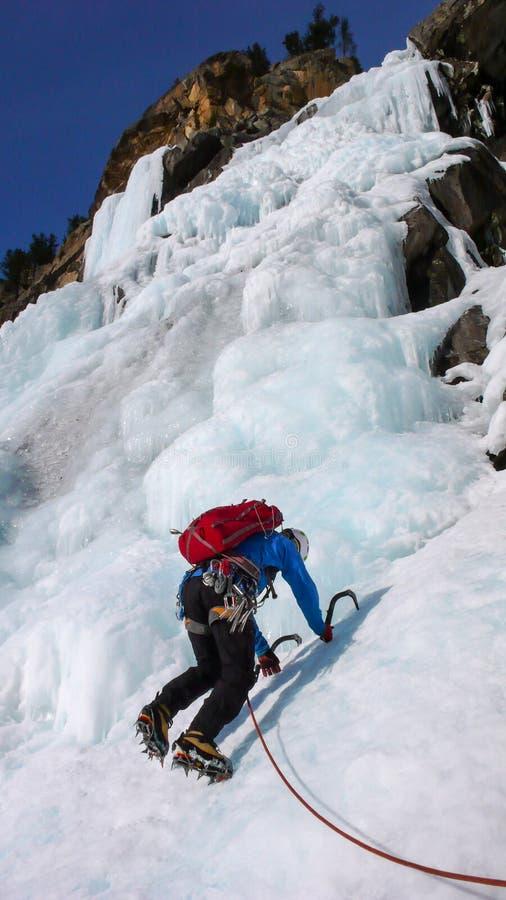 Manlig isklättrare i ett blått omslag på en ursnygg fryst vattenfallklättring i fjällängarna i djup vinter arkivfoto