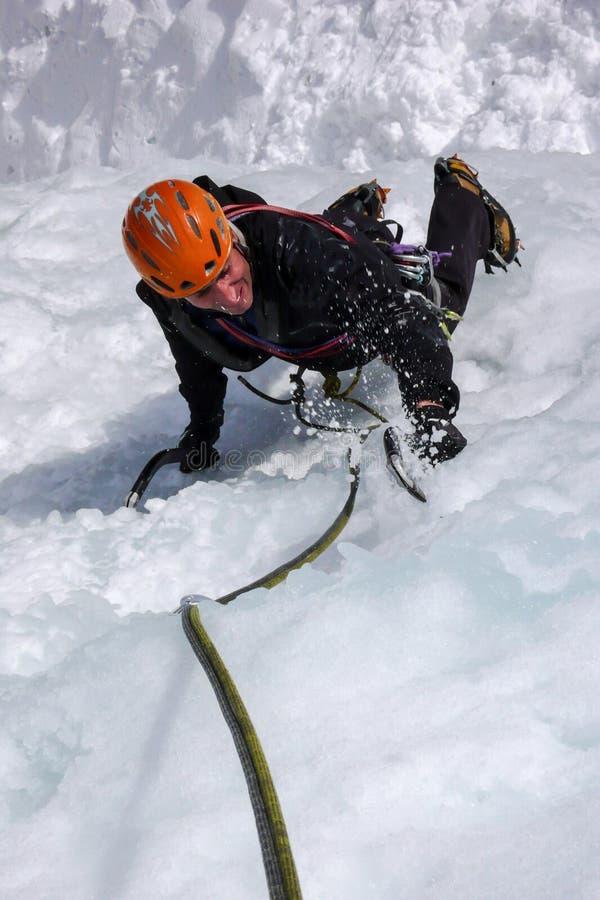Manlig isklättrare på en brant fryst vattenfall på en härlig vinterdag i de schweiziska fjällängarna royaltyfri fotografi