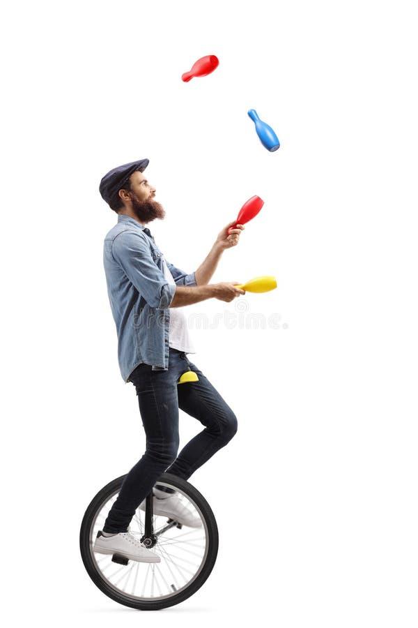 Manlig jonglör på en enhjuling som jonglerar med klubbor royaltyfri foto