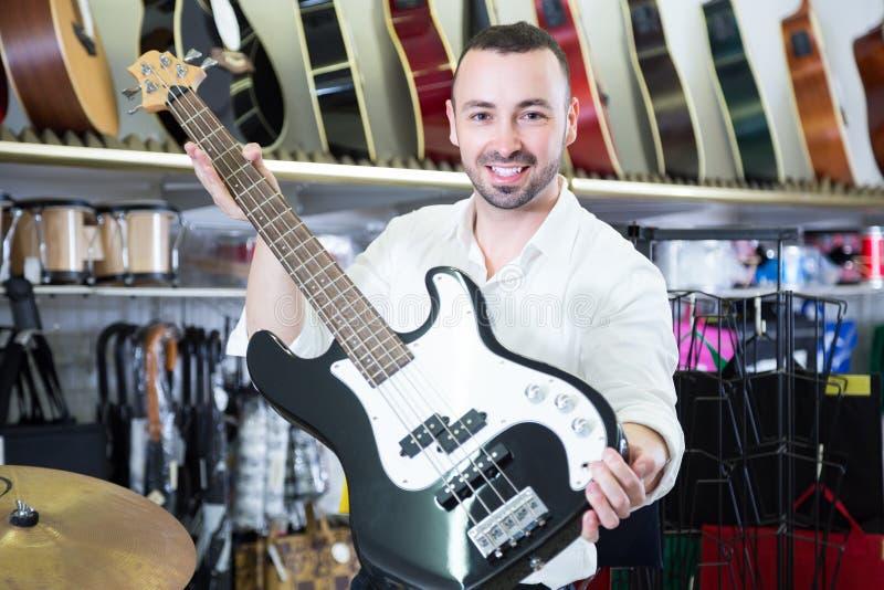 Manlig köpare som väljer gitarren i lager royaltyfri bild