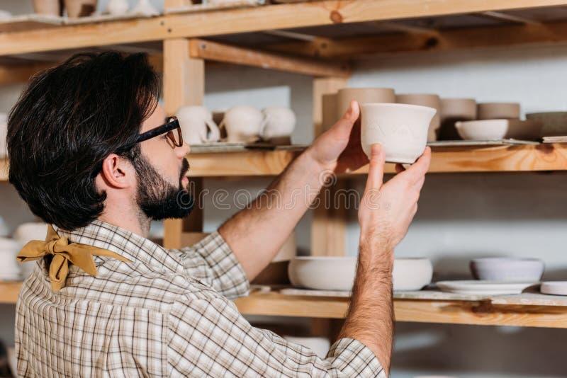 manlig keramiker med den keramiska dishwaren på hyllor i seminarium arkivbild
