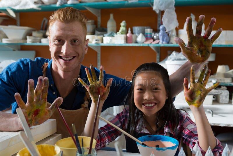 Manlig keramiker och flicka som visar deras målade händer royaltyfri bild