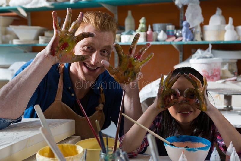 Manlig keramiker och flicka som visar deras målade händer royaltyfria bilder