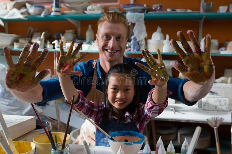 Manlig keramiker och flicka som visar deras målade händer arkivfoton