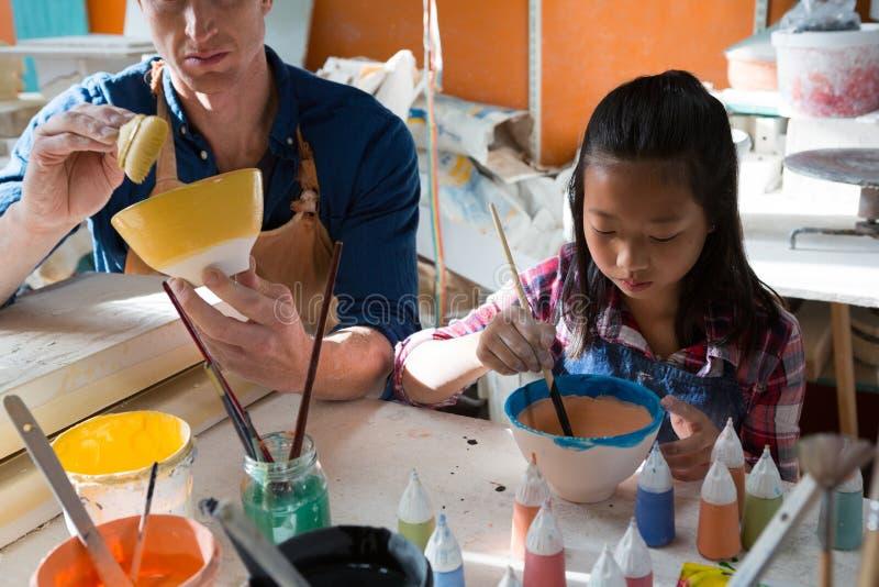 Manlig keramiker- och flickamålningbunke arkivfoto