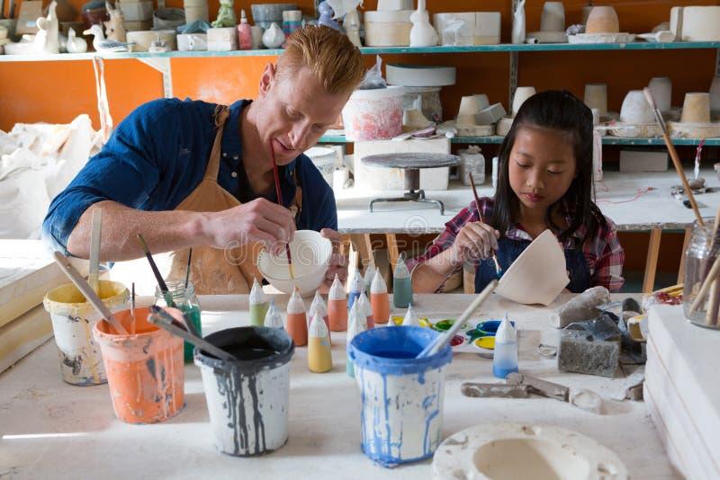 Manlig keramiker- och flickamålningbunke arkivfoton