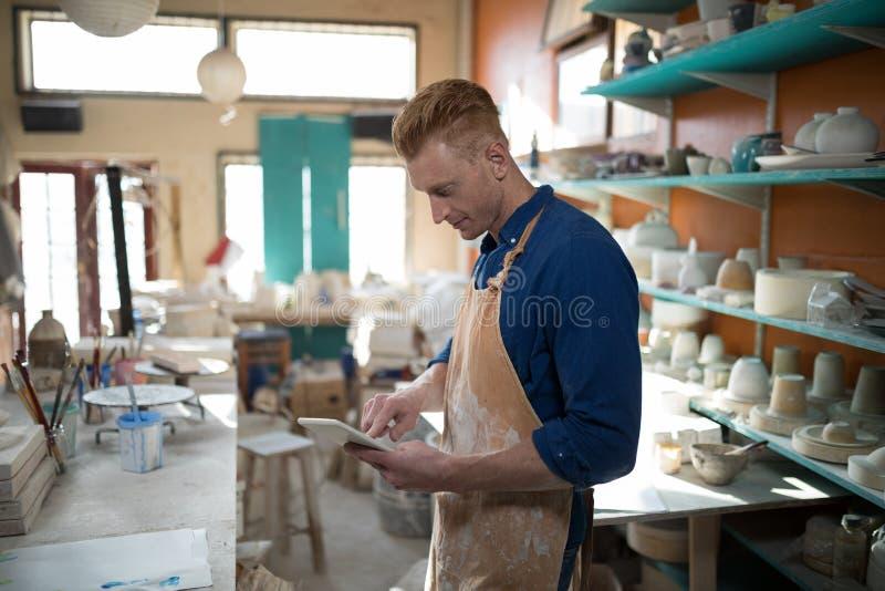 Manlig keramiker som använder den digitala minnestavlan arkivfoto