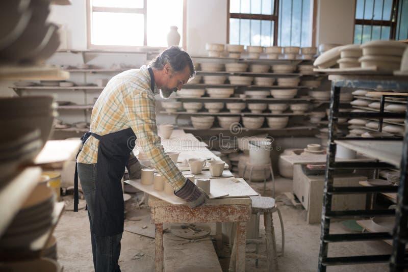 Manlig keramiker som arbetar på worktop fotografering för bildbyråer