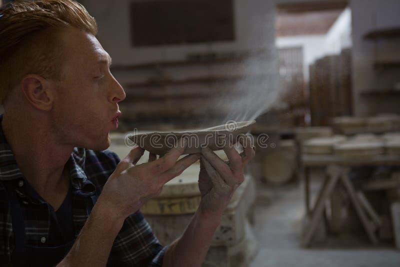 Manlig keramiker som blåser damm från en bunke fotografering för bildbyråer