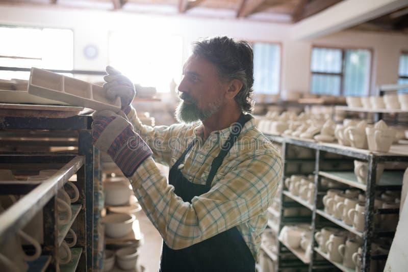 Manlig keramiker som förlägger hantverkprodukten på hylla royaltyfri bild