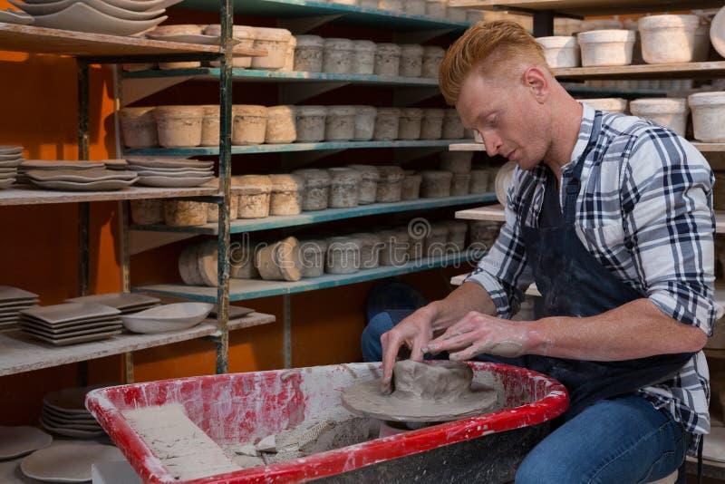 Manlig keramiker som gör en kruka fotografering för bildbyråer