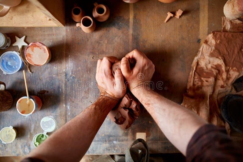 Manlig keramiker som gjuter en lera i krukmakeriseminariet, närbild, selektiv fokus royaltyfri foto