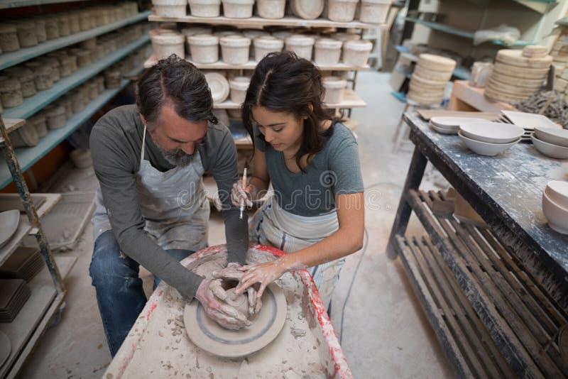 Manlig keramiker som hjälper den kvinnliga keramikern arkivbilder