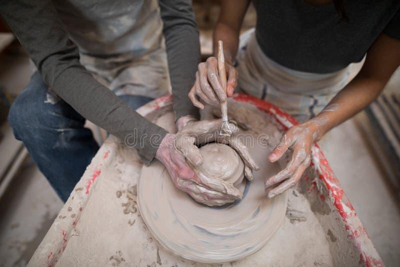 Manlig keramiker som hjälper den kvinnliga keramikern arkivfoton