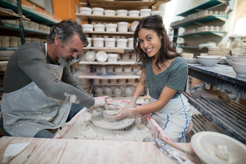 Manlig keramiker som hjälper den kvinnliga keramikern fotografering för bildbyråer