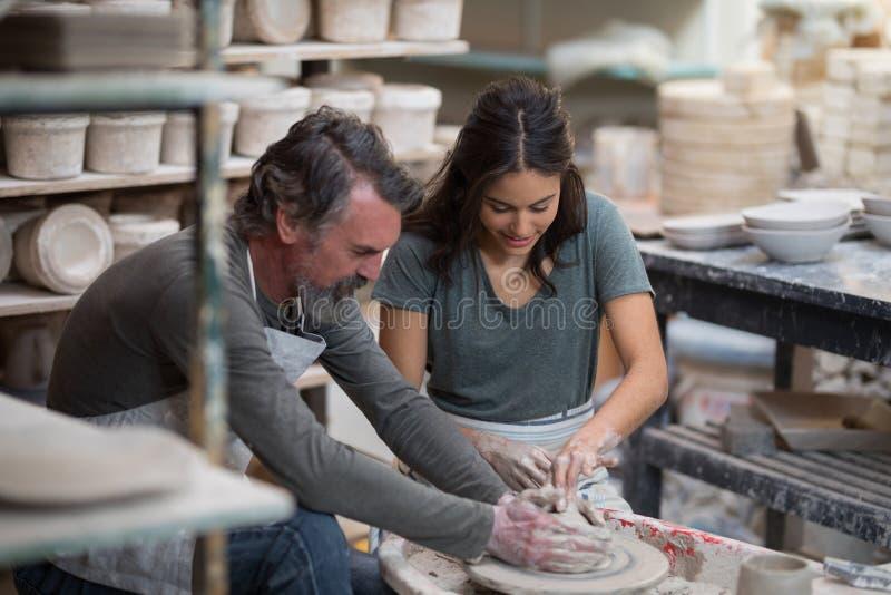 Manlig keramiker som hjälper den kvinnliga keramikern royaltyfria foton