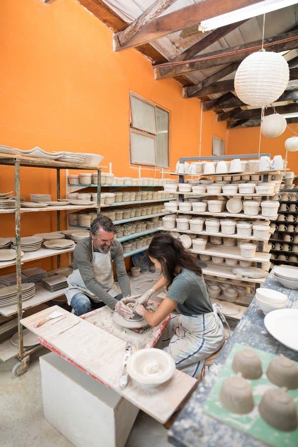 Manlig keramiker som hjälper den kvinnliga keramikern royaltyfri foto