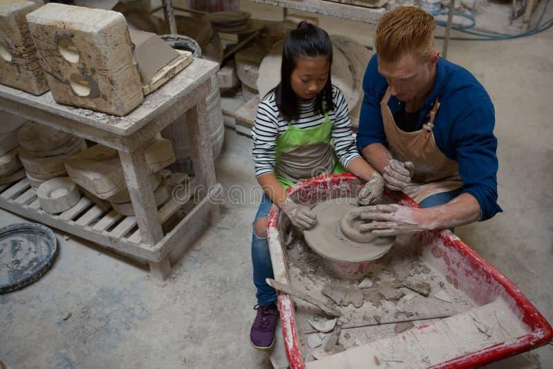 Manlig keramiker som hjälper flickan, i att gjuta en lera arkivfoton