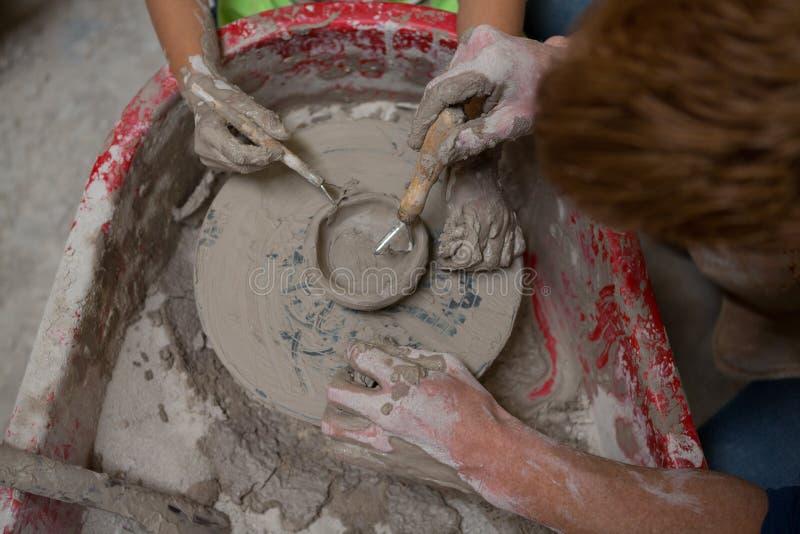 Manlig keramiker som hjälper flickan, i att gjuta en lera fotografering för bildbyråer
