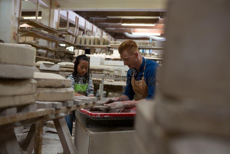 Manlig keramiker som hjälper flickan, i att gjuta en lera royaltyfri bild