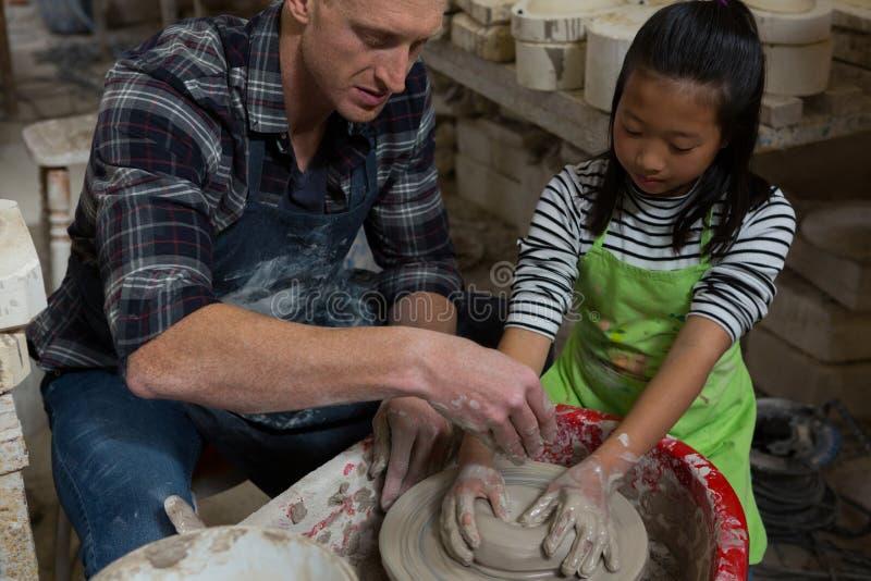 Manlig keramiker som hjälper flickan, i att gjuta en lera royaltyfria bilder