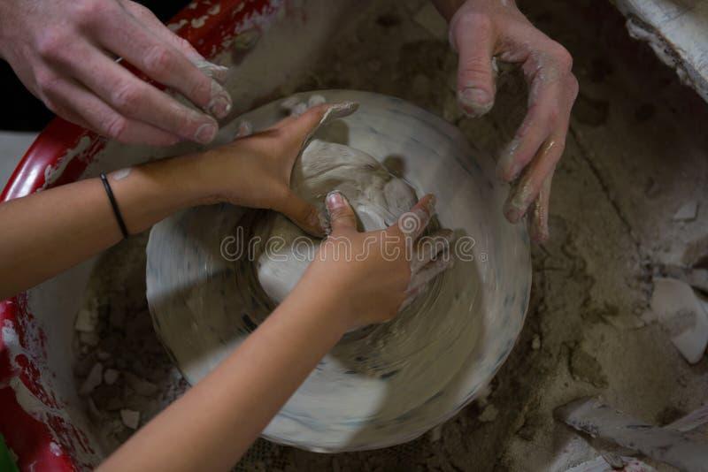 Manlig keramiker som hjälper hans dotter, i framställning av en kruka arkivfoton
