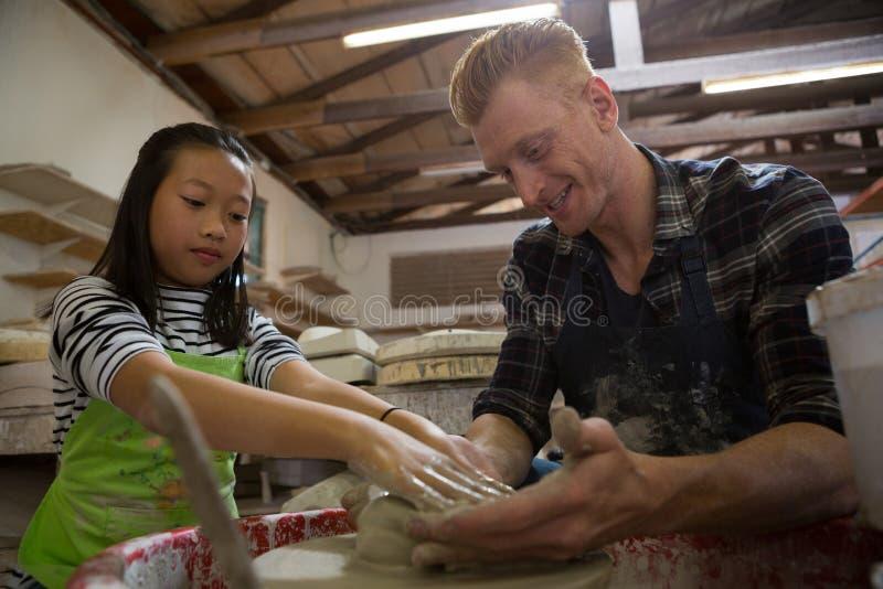 Manlig keramiker som hjälper hans dotter, i framställning av en kruka royaltyfri bild